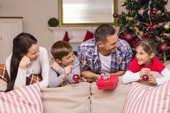 Familia sonriente que se inclina en el sofá Foto de archivo libre de regalías