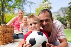 Familia sonriente que se relaja en una comida campestre Foto de archivo libre de regalías