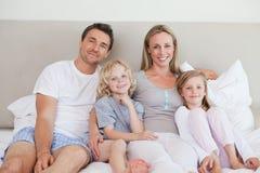 Familia sonriente que se sienta en la cama Fotos de archivo