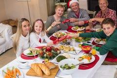 Familia sonriente que tira de las galletas de la Navidad en la tabla de cena Imagen de archivo