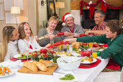 Familia sonriente que tira de las galletas de la Navidad en la tabla de cena Foto de archivo