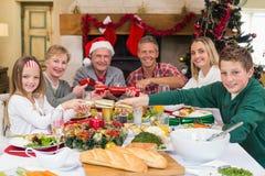Familia sonriente que tira de las galletas de la Navidad en la tabla de cena Imágenes de archivo libres de regalías