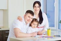 Familia sonriente que une en casa Imagen de archivo libre de regalías