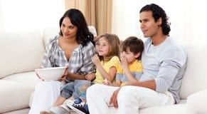 Familia sonriente que ve la TV en el sofá Imágenes de archivo libres de regalías