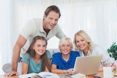 Familia sonriente usando el ordenador portátil junto para hacer la preparación Fotografía de archivo