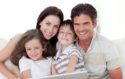 Familia sonriente usando una computadora portátil Fotografía de archivo libre de regalías
