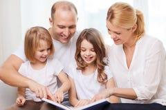 Familia sonriente y dos niñas con el libro Fotos de archivo libres de regalías