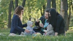 Familia sueca con el pequeño hijo que se relaja en la sobrecama en parque metrajes