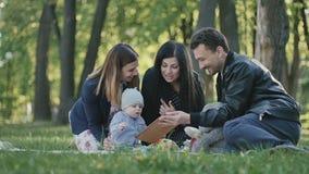 Familia sueca joven que se relaja con el niño pequeño en la sobrecama en parque almacen de metraje de vídeo