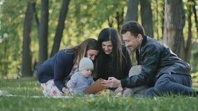 Familia sueca joven que se relaja en parque verde con el pequeño hijo metrajes
