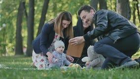 Familia sueca linda que se relaja con el pequeño hijo en un parque almacen de metraje de vídeo