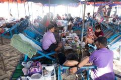 Familia tailandesa que come el almuerzo asentado en la playa Imagen de archivo