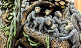 Familia tallada del mono en la madera en la textura de madera del fondo Imágenes de archivo libres de regalías