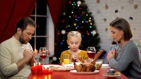Familia tradicional que ruega antes de la cena de Navidad, creencia en dios, cristianismo fotografía de archivo libre de regalías