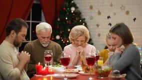 Familia tradicional que ruega antes de la comida de la Navidad, creencia en dios, cristianismo metrajes