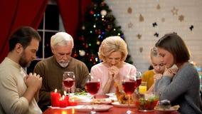 Familia tradicional que ruega antes de la comida de la Navidad, creencia en dios, cristianismo imágenes de archivo libres de regalías