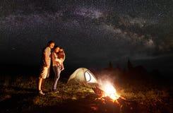 Familia turística con la hija que tiene un resto en montañas en la noche debajo del cielo estrellado con la vía láctea foto de archivo libre de regalías