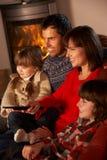 Familia TV de observación de relajación por el fuego de registro acogedor Imágenes de archivo libres de regalías