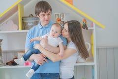 Familia unida agradable de mamá, de papá y de hija presentando en su sitio blanco fotos de archivo libres de regalías