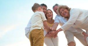 Familia unida que pone las manos juntas almacen de video