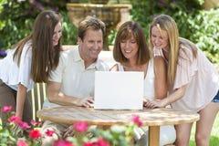 Familia usando el ordenador portátil afuera en jardín Imagenes de archivo
