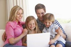 Familia usando el ordenador portátil en Sofa At Home Fotos de archivo