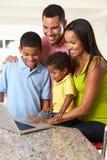 Familia usando el ordenador portátil en cocina junto Foto de archivo libre de regalías