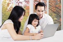 Familia usando el ordenador portátil en la tableta en casa Imágenes de archivo libres de regalías