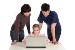 Familia usando la computadora portátil Imágenes de archivo libres de regalías