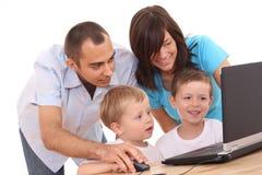 Familia usando la computadora portátil Fotografía de archivo libre de regalías