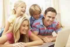 Familia usando la computadora portátil en el país junto Imágenes de archivo libres de regalías