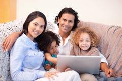 Familia usando la computadora portátil en el sofá junto Imagen de archivo libre de regalías