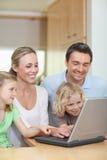 Familia usando la computadora portátil en la cocina Imagen de archivo