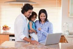 Familia usando la computadora portátil en la cocina junto Fotografía de archivo
