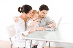 Familia usando la computadora portátil Fotografía de archivo