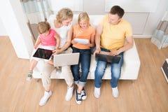 Familia usando las tabletas y los ordenadores imagenes de archivo