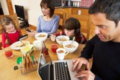 Familia usando los adminículos mientras que come el desayuno imagen de archivo