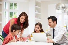 Familia usando los dispositivos de Digitaces en el desayuno Imagenes de archivo