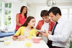 Familia usando los dispositivos de Digitaces en la mesa de desayuno Fotografía de archivo libre de regalías