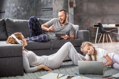 Familia usando los dispositivos digitales Fotografía de archivo libre de regalías