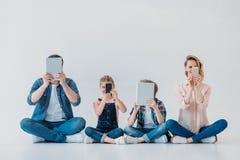 Familia usando los dispositivos digitales mientras que se sienta en el piso Foto de archivo libre de regalías