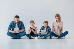 Familia usando los dispositivos digitales mientras que se sienta en el piso Fotos de archivo libres de regalías