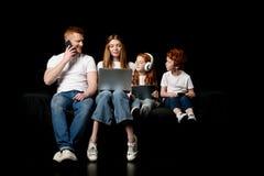 Familia usando los diversos dispositivos digitales Fotografía de archivo