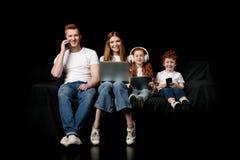 Familia usando los diversos dispositivos digitales Imagenes de archivo