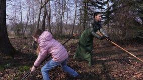 Familia usando los rastrillos para las hojas que recoge trabajos que cultivan un huerto almacen de metraje de vídeo