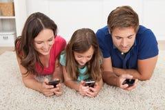 Familia usando los teléfonos elegantes en casa Foto de archivo libre de regalías
