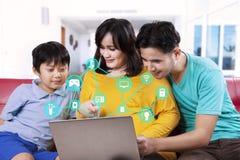 Familia usando sistema casero elegante en el ordenador portátil Fotografía de archivo