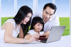 Familia usando tarjeta de crédito al pago en línea Fotografía de archivo libre de regalías