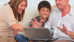 Familia usando un ordenador portátil para jugar a un juego almacen de metraje de vídeo