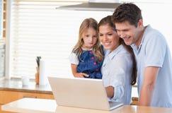 Familia usando una computadora portátil Fotos de archivo libres de regalías